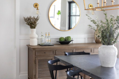 Modern farmhouse dining room with brass fixtures and marble table