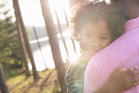 腕の中で子供を運ぶ男