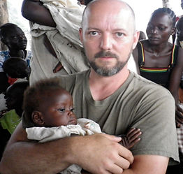 Tom Kilian of Mercy Partners holding South Sudanese child during medical clinic