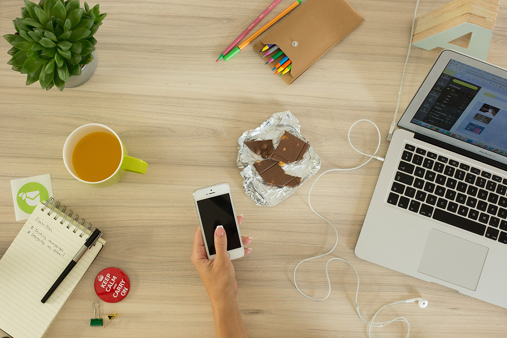 Person working with phone, chocolate, tea distractions, causing procrastination