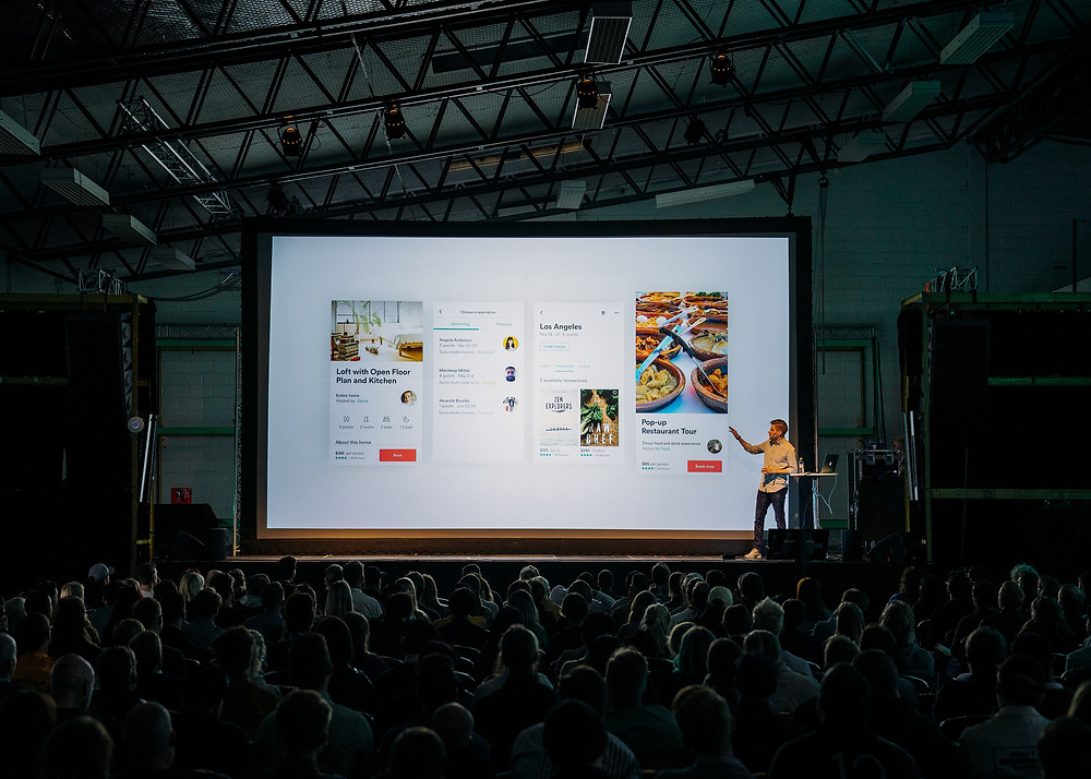 Man is presenting in front of a large screen and large audience in a warehouse building.