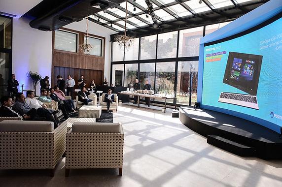 Lounge composto para público VIP, com painel de LED curvo e mobiliário diferenciado