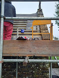Person standing on porch scaffold