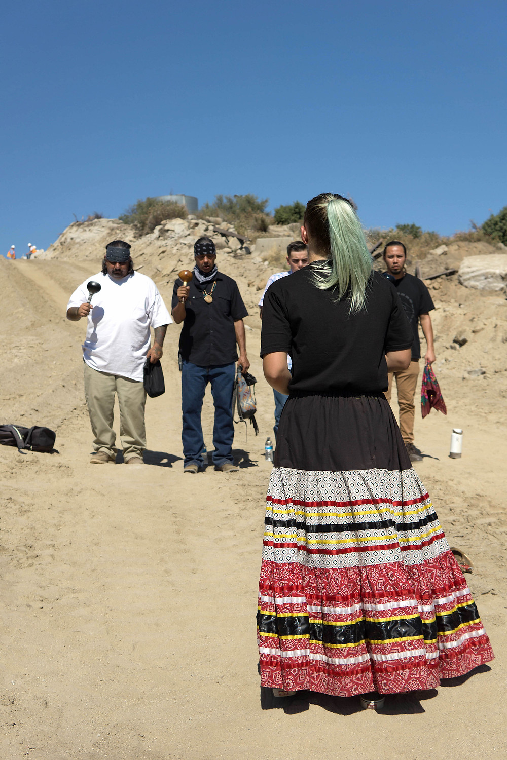 Baines and other Kumeyaay tribal members in ceremony near border wall construction. (Credit: James Stout)