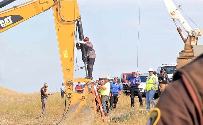 Indigenous activist locked to DAPL construction equipment, 2016. (Credit: Desiree Kane/Wikimedia Commons)