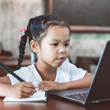 Cute asian child girl using laptop and w