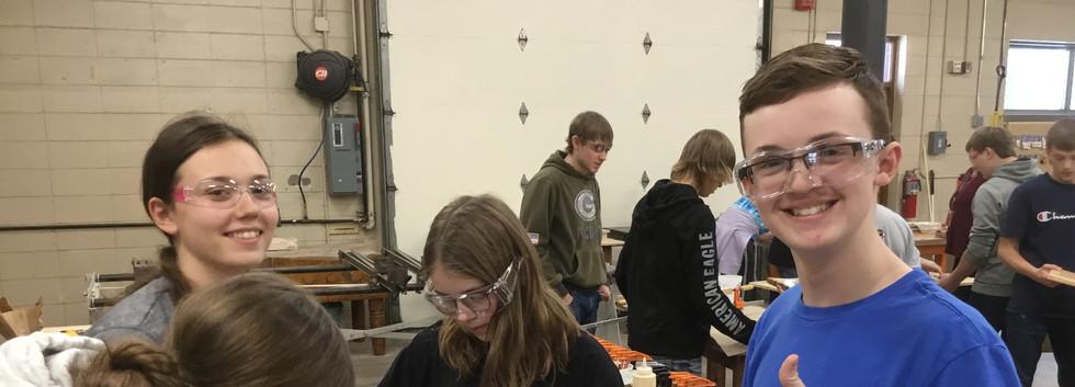 Olivia, Sydney, Greyson, and Serena working on cutting boards