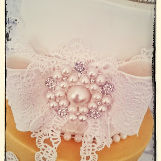 gold and white lace wedding cake close up