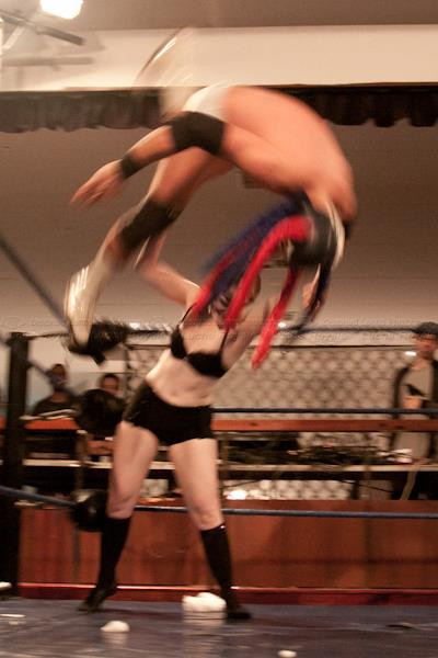 A woman throwing a large wrestler to the ground