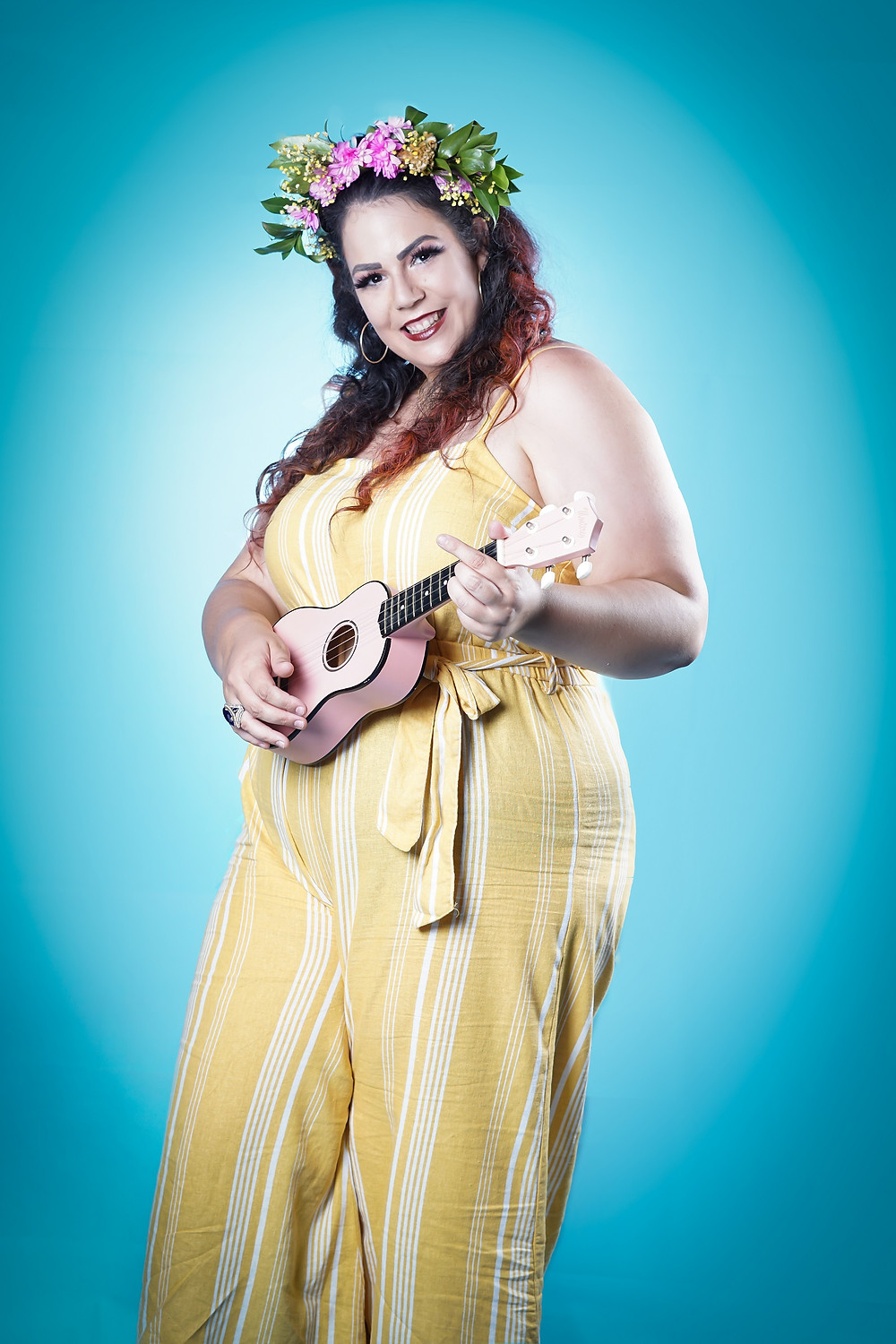 Me wearing a nice yellow jumpsuit, flower crown, and make up. I'm playing a tiny pink ukulele.