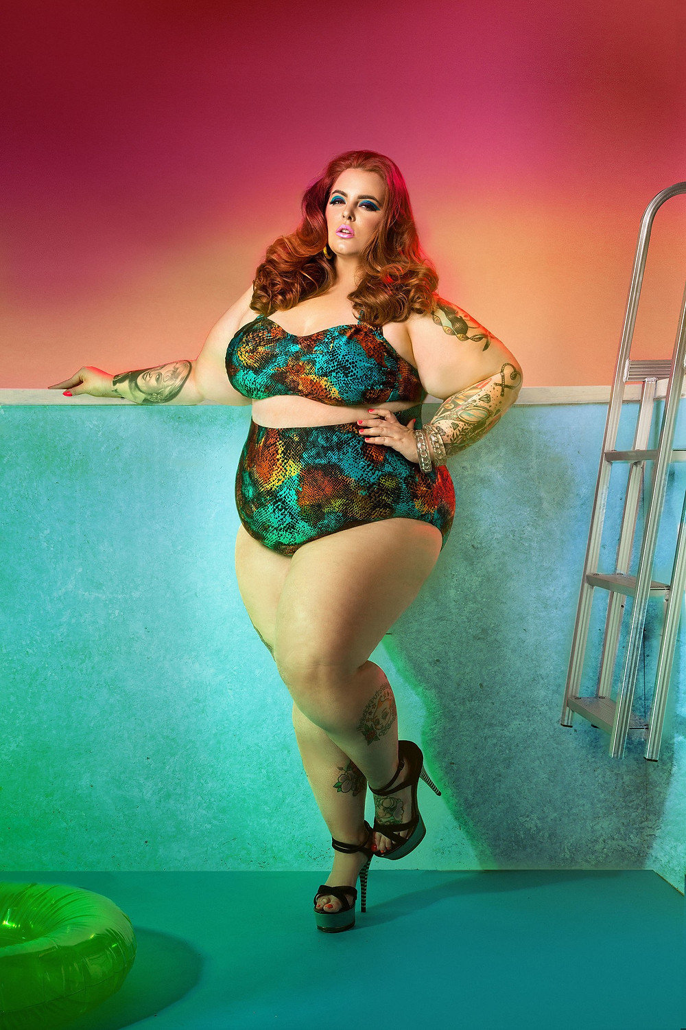 A plus-sized model with red curled hair stands in a bikini and stilettos, in an empty pool. The lighting in this shot is also just.. Hnggg.