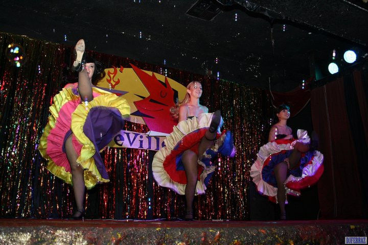 Three dancers performing the cancan