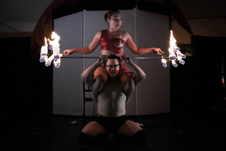 Woman sitting on a man's shoulders, both are holding lit fire dance props