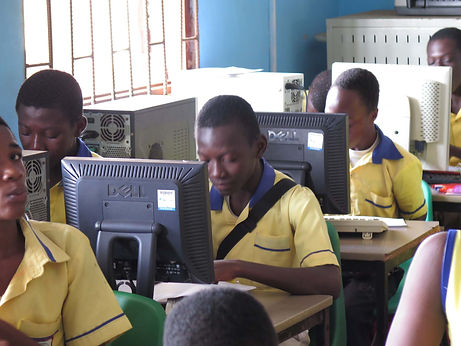 Students writing on computers in Ghana