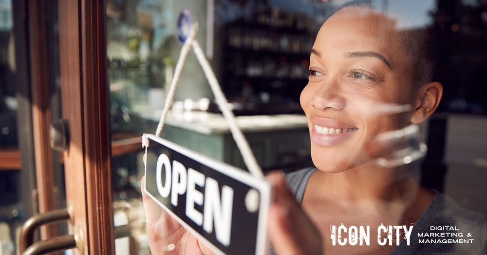 Picture of african american woman holding open sign to promote coachella valley and palm srpings back business listing