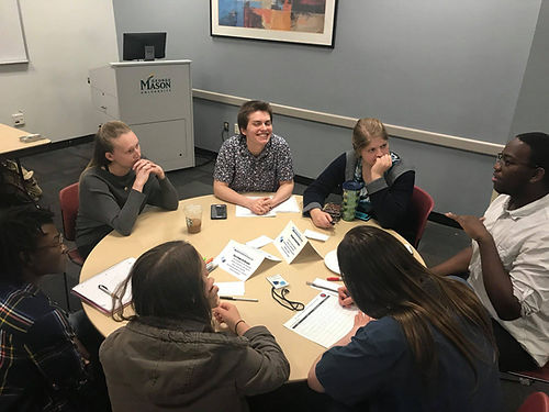 A group of six students sit around a table in the middle of a discussion. There is a podium in the background with the George Mason University logo. Five students are listening to a student speak and are either smiling or look thoughtful.