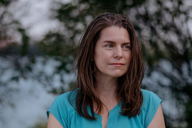 A headshot of Anna Clark, a white woman. She is looking to the left with a slight smile. She is in a blue shirt with shoulder length brown hair. The background are some blurred tree branches.