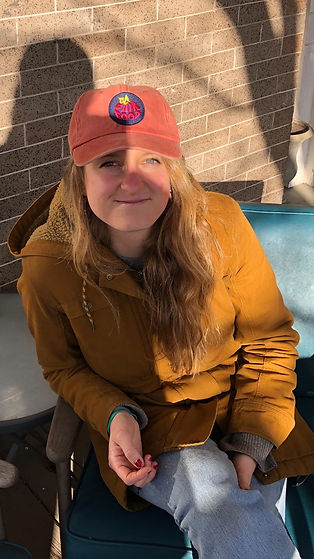 A picture of Izzy Moody. She is a white woman with blonde hair. She is sitting in a chair with a yellow jacket and a hat that says DC Fair Food.
