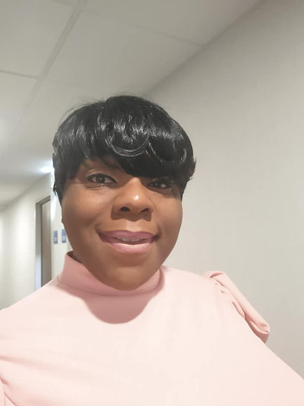 A headhsot of Bekura Shabazz Branch, an African American woman standing in the hallway. She is wearing a pink top and has short black hair with bangs. She is smiling and looking directly at the camera.