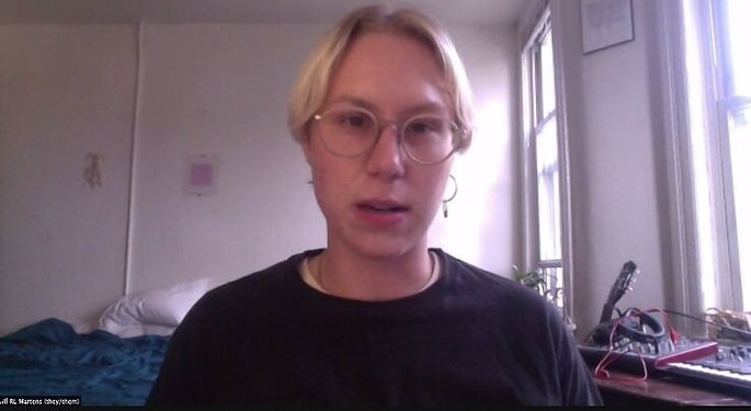 A headshot of R. L. Martins, a white individual. They have on a gray sweater and oval shaped glasses. They are looking at the camera and look like they are in the middle of speaking. They have short blonde hair parted in the middle and hoop earrings. In the background, they have a bed, two windows, and a guitar.