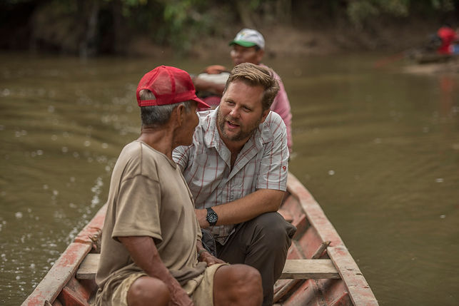 This is an image of Dr. Gilmore, a white man, on a wooden boat with two individuals of the Maijuna indigenous group of the Peruvian Amazon. The man in the front has on a brown shirt and red cap. Dr Gilmore has brown hair and a beard and is talking to man in the front. The third individual is wearing a pink shirt and green cap and is sitting by the motor.