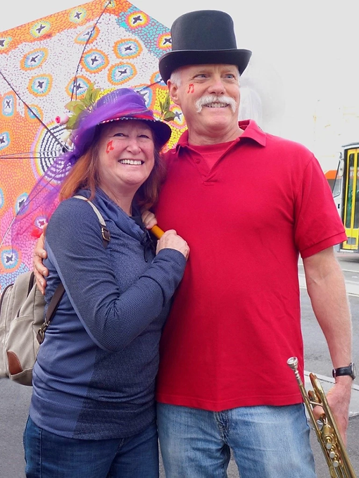 Ken Brandt and Judy Brandt giving each other a little hug just before a New Orleans style jazz parade. Judy is wearing a New Orleans 2nd line hat ane sporting a colorful parasol. Ken is wearing a top hat and holding his trumpet. Both have a red musical note face painted on their right check by Judy.