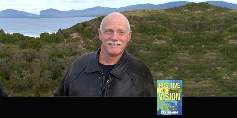 """Author Ken Brandt with the Tasmanian hills and ocean in the background. Superimposed in the lower front right is the book cover of Ken's book """"Positive Vision: Enjoying the Adventures and Advantages of Poor Eyesight""""."""