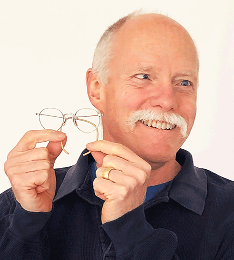 Author Ken Brandt as a smiling adult holding up his 60 plus year old very first pair of eyeglasses