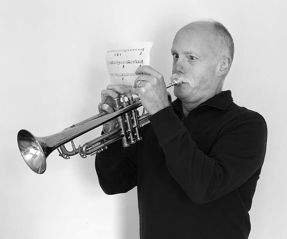 Author Ken Brandt playing trumpet while holding sheet music very close to his eyes in order to read it