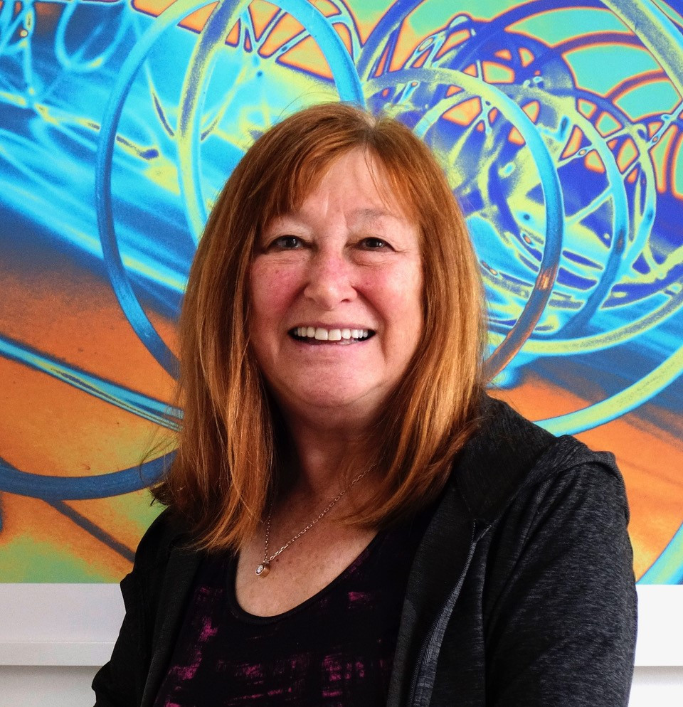 Judy Brandt in front of one of her colorful abstract photography artworks