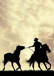 Cowboy on horseback with clouds in the background. While riding his horse, he is leading another horse by its reins.
