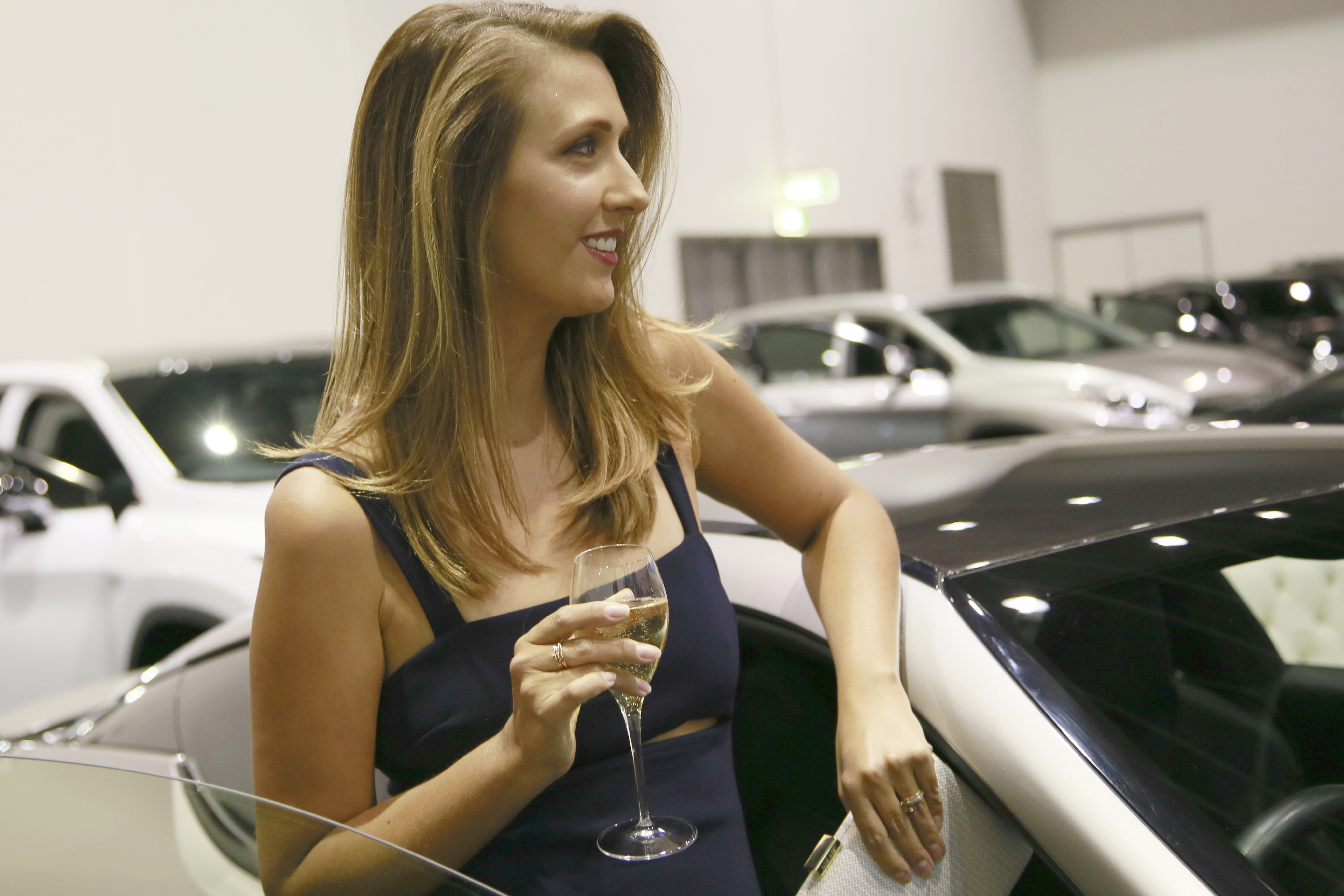 Woman with champagne glass and luxury cars
