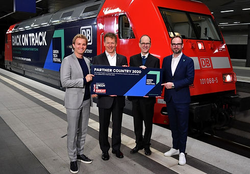 Four people posing in front of a Deutsche Bahn train holding the Green is Great logo