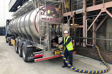 Man feeding a pump into a tanker truck