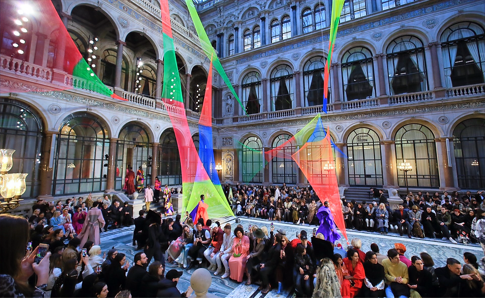 People watching and participating in a fashion show in a grand hall with colourful streamers hanging from the ceiling