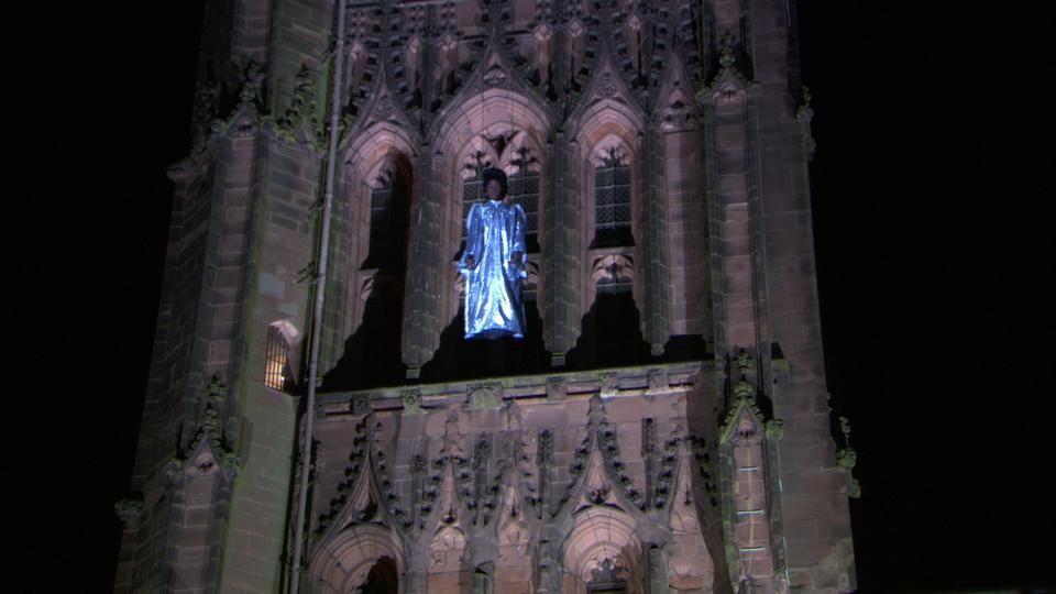 A child in an angel costume being lowered from the spire of a cathedral