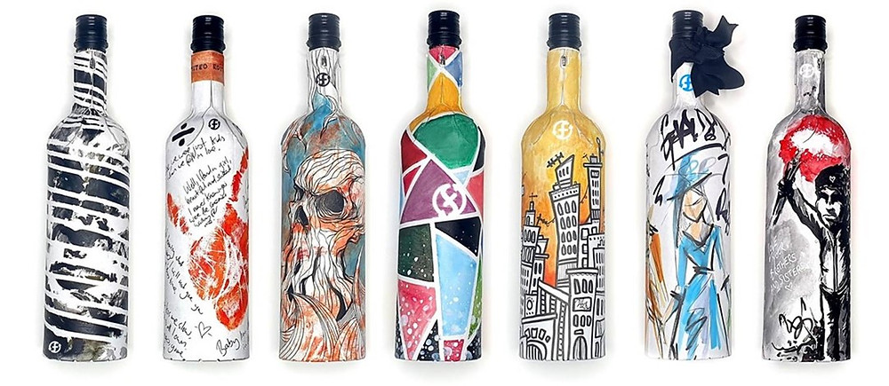 Seven wine bottles made from paper each with a different design