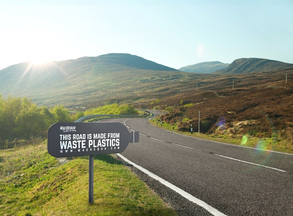 A road with a sign reading 'This road is made from waste plastic'