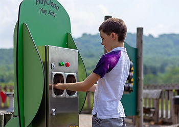 Child cleaning their hands at a hand sanitiser station