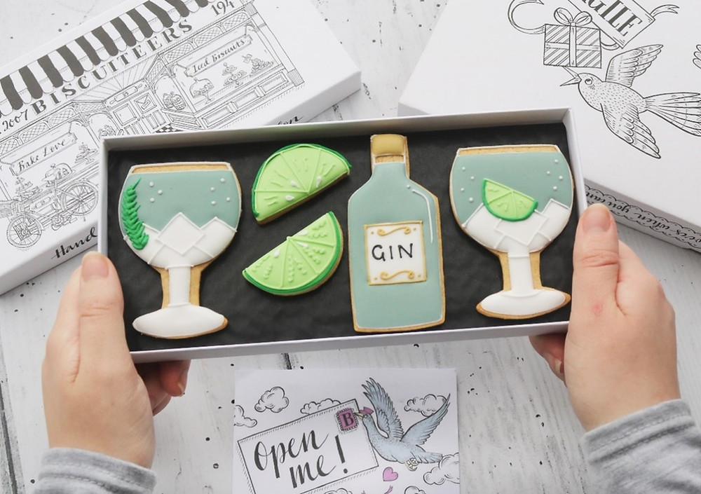 A box of four biscuits with two biscuits in the shape of gin glasses with ice cubes and botanicals made of icing, two biscuits in the shape of wedges of limes, and one biscuit in the shape of a bottle of gin