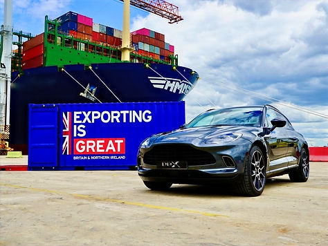 Aston Martin SUV in front of Exporting is Great branded shipping container