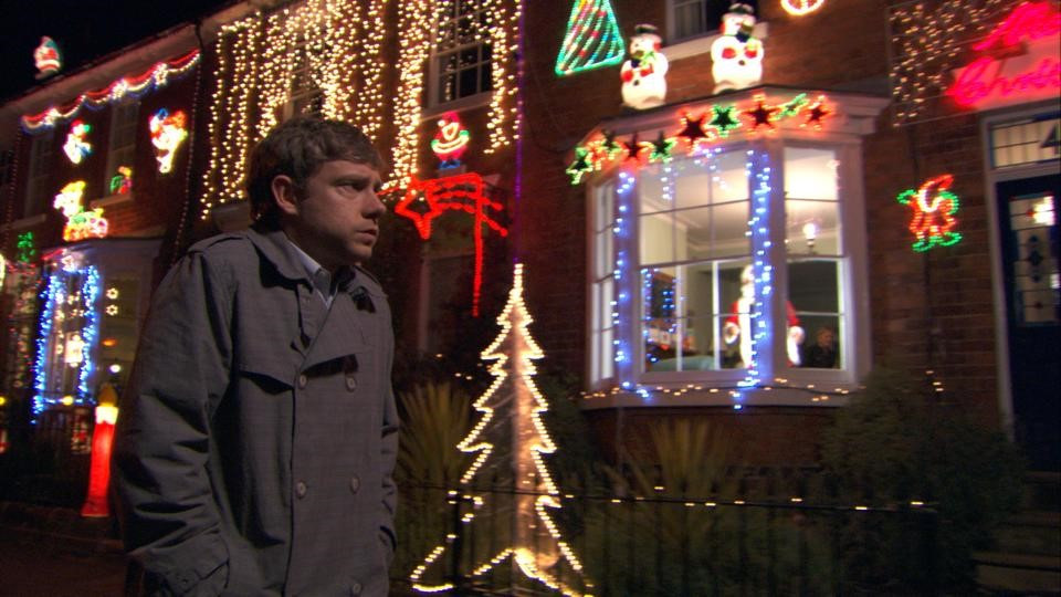 A man walking past houses decorated with Christmas lights