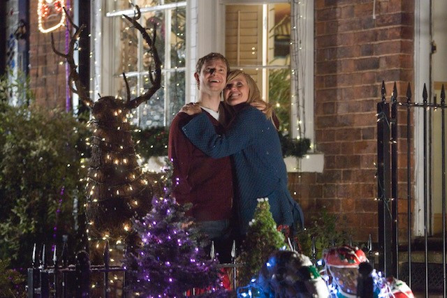 Two people hug in front of a house surrounded by Christmas lights