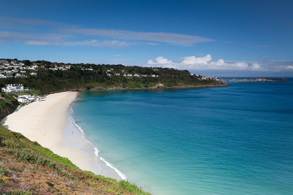 A sand beach and blue ocean in Cornwall, UK