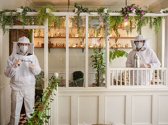 People wearing beekeeper suits and facemasks at a restaurant