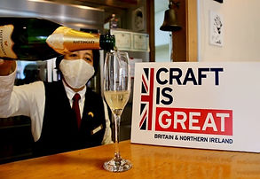 Man with the mask pouring champagne into the glass by the Craft is GREAT sign