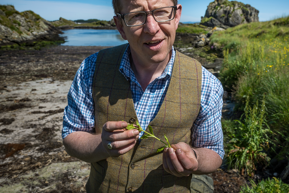 The Botanist's local forager James Donaldson stood outside on the island of Islay holding locally sourced botanicals