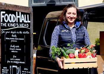 Woman standing in front of a pub holding a small crate of vegetables