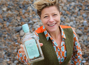 Woman holding up a bottle of gin