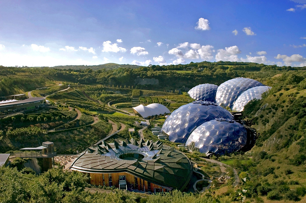 Glass domes in a green valley. The domes house an indoor rainforest